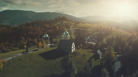 карпатская : Sunset Mountain Village Church Scenery Aerial View. Panoramic Autumn Wild Nature Hill Landscape Overview. Rural High Meadow Unpolluted Environment, Tourism Concept. Drone Back Flight Footage 4K (UHD)