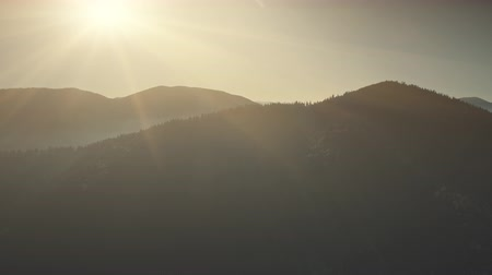 Mountain Peak Range Sunrise Soft Light Aerial View. Rock Surface Scenery Wildlife Habitat Sun Beam Overview. Fir Tree Wood Highland Forest Cliff Clean Ecology Concept Drone Flight Footage 4K (UHD)