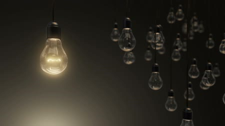 Idea concept with light bulbs on black dark background, one against many confrontation