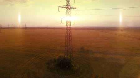 obrys : AERIAL High-voltage tower summer warm evening light camera fly up near metal structure contour opposite sun