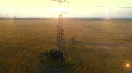 oposto : AERIAL High-voltage tower summer warm evening light camera fly up near metal structure contour opposite sun natural native