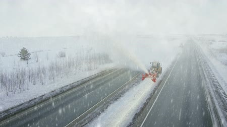 snow plow : Heavy big storm snow fall, grader clean remove snow, snowplow, snow blower, blast snowfall, winter, road, special vehicle on the highway, cool frozen fountain of snow aerial view Stock Footage