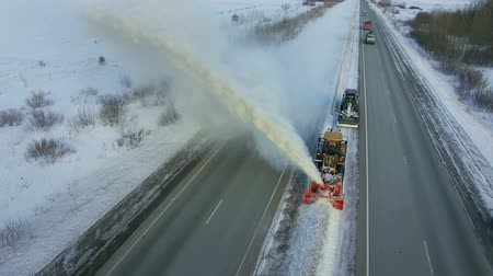 Grader clean remove snow, snowplow, snow blower, blast snowfall, winter, road, special vehicle on the highway, cool frozen fountain of snow aerial view
