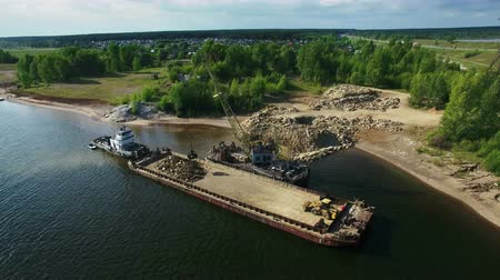 Dry cargo ship bulk carrier crane load crushed stones rock in river dock aerial view fly right