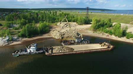 macadam : Dry cargo ship bulk carrier crane load crushed stones rock in river dock aerial view fly right