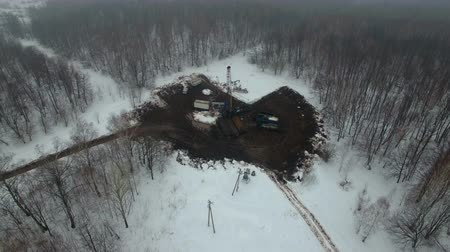 petróleo : Drilling a deep well with a drilling rig in an oil and gas field in winter forest. The field is located in Kamchatka, Tundra, Yamal, North, West, Siberia, fog, smoke, aerial Vídeos