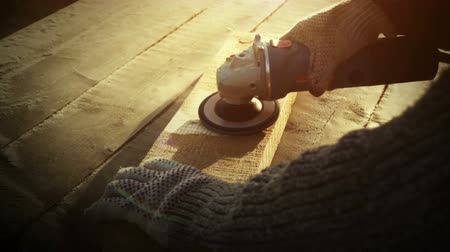 knitted gloves : Angle grinder tool, brutal carpenter man polishes a rough plank on a wooden table at sunset. Rapid 100 fps Stock Footage