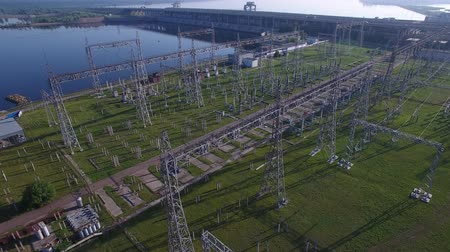 transzformátor : Electric substation, hydroelectric power station, bridge over river, electric tower, power distribution. Cars and trucks traffic, fog early morning spring summer sun. Aerial quadrocopter flying over. Stock mozgókép