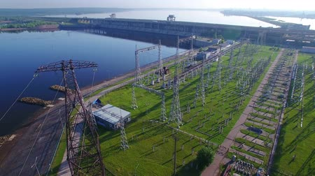 напряжение : High voltage electric power tower close up and fly out, electric substation, hydroelectric power station, power distribution. Aerial quadrocopter. Cars and trucks traffic, early morning summer sun.