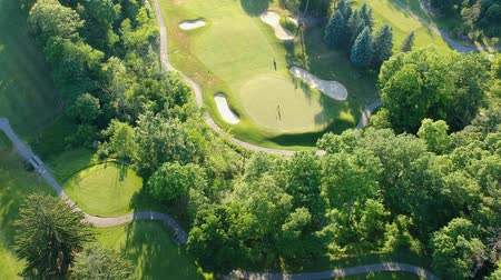 golfjátékos : Golf course with two player in the evening. Eye bird view from the sky. Aerial footage of park forest and golf course. Stock mozgókép