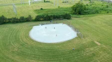 american football player : Aerial view of the baseball diamond field with group of players at summer evening. Green clean baseball sport stadium in the city park bird eye view. Canada, Ontario. Stock Footage