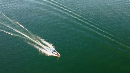 prędkość : Overhead drone footage the white boat fast sails over the sea, leaving a white trail at the sunny day.