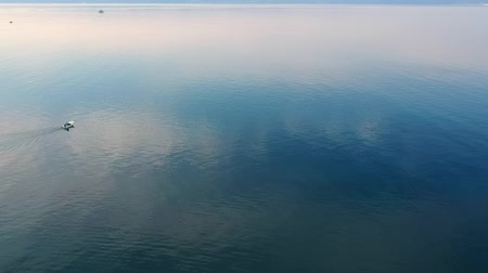 sessiz : Fisherman on his boat moving in calm sea water at amazing morning for fresh mussels. Aerial bird view of coastal waters in Croatia.