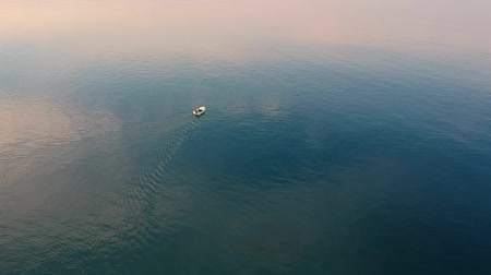 midye : Fisherman on his boat moving in calm sea water at amazing morning for fresh mussels. Aerial bird view of coastal waters in Croatia.