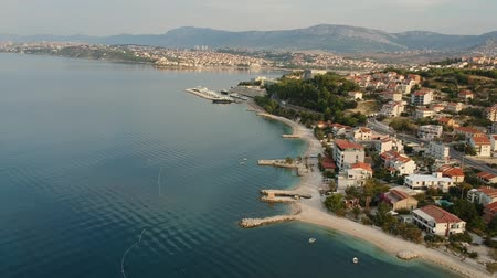 адриатический : Scenic aerial bird view at morning coastal village near Split in Croatia, calm and quite tourist vocational hotel seafront under green mountains in Europe. Early morning. Стоковые видеозаписи
