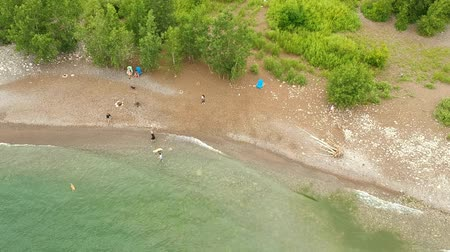 bezmotorové létání : Aerial flying above water sandy beach coast on the sea shore with some people walking and enjoy the calm day near water. Drone gliding over.