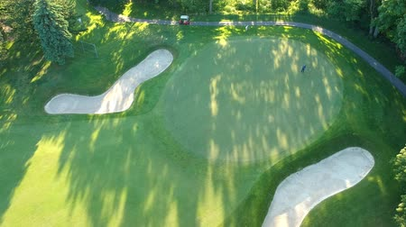 golfové hřiště : Golf course with two player in the evening. Eye bird view from the sky. Aerial footage of forest and golf course. Dostupné videozáznamy