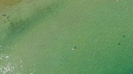 ostrovy : View of a tropical beach from above. Aerial view of relaxed people swimming on a clear and transparent sea. Bird eye photo from above.