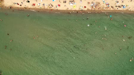 escala : View from above, aerial view of green water with a sandy beach with beach umbrellas and people, kids and tourists who relax and swim.