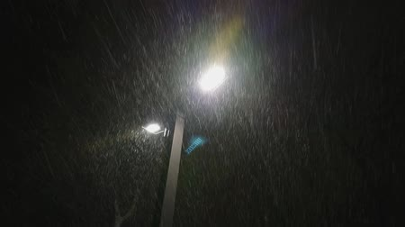 mrożonki : Extreme snow storm and wind gust in the city against street lights or lamps, exposing direction of the snowflakes speed and movement. Night. Wideo
