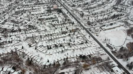 fenomen : Aerial view of the roads and people houses below at snow storm, winter weather alert day. City road aerial view taken from above scenery. Top bird view suburb urban housing development. Stok Video