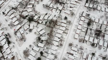 télen : Aerial view of the roads and people houses below at snow storm, winter weather alert day. City road aerial view taken from above scenery. Top bird view suburb urban housing development. Stock mozgókép