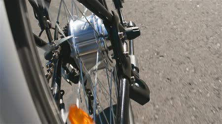 electromotor : Electric bicycle motor spins close up. E bike motor rotation while riding without peddling in sunny summer day. Electric wheel in details. Stock Footage