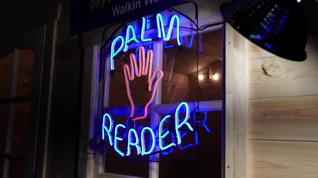 kultusz : Neon light palm reader fortune teller sign on the window with flashing palm. Stock mozgókép