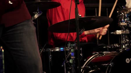 Drummer plays drums on the rock concert. Male drummer hands with drumstick close up in the rhythm of the music. Drum plate on the stage. Rock band performing. Slow motion.