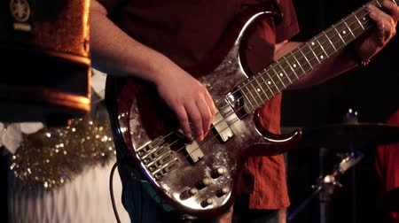 Male guitar player on stage at a concert playing electric bass guitar. Close up of music instrument. Guitarist hits the strings of the guitar at rock festival. Slow motion.