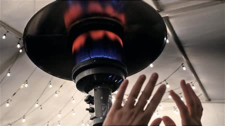Woman is warming her hands near an artisan winter gas lamp fireplace or kerosene lamp outdoors, Decorative restaurant gas flame outdoor with led Christmas lights on the background. Slow motion. Vídeos