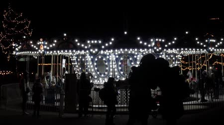 Brightly lit flashing light vintage carousel at winter light festival or carnival fair, spinning wheel and going round with horse ride at amusement park. Silhouettes of parents and kids making selfie