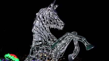 мифический : Unicorn rearing statue made of winter Christmas decorations garlands or neon lights. Light festival in Toronto, Ontario, Canada, amusement park, Ontario place theme park. A lot of light bulbs. Стоковые видеозаписи