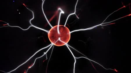 View of plasma ball with moving energy rays inside on black background. Abstract lightning in colors. Electricity in gas.