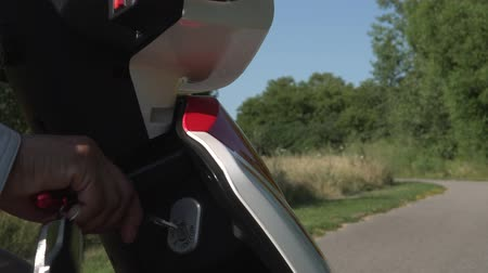 スクーター : Female turning the key of electric scooter to start motor and riding in the city park at summer evening. Mobility device on the road. Red stylish Environmentally conscious e vehicle. 動画素材