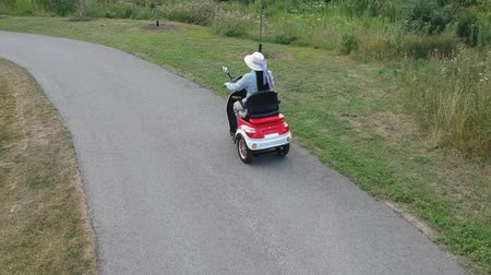 Disabled person driving a motorized mobility scooter for elderly and or disabled in the green park. Recreational electric ability vehicle for handicapped. Accessibility concept.