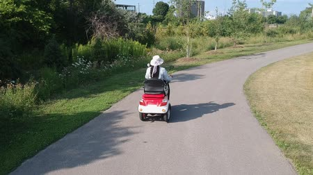 Disabled person driving a motorized mobility scooter for elderly and or disabled. Recreational electric ability vehicle for handicapped footage movement from behind aerial. Accessibility concept. Vídeos
