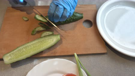 chalota : Cucumber cutting. Preparation of salad from fresh vegetables of cucumbers, tomato and onions shallot