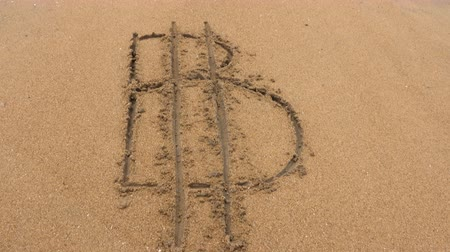 pegadas : Bitcoin cryptocurrency sign written on sand. Sea wave washes away the inscription Bitcoin. Top view