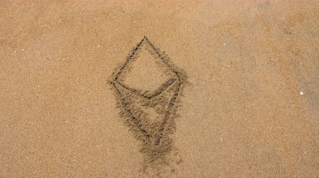 pegadas : Ethereum cryptocurrency written in the sand. Sea wave washes away the inscription Ethereum. Top view