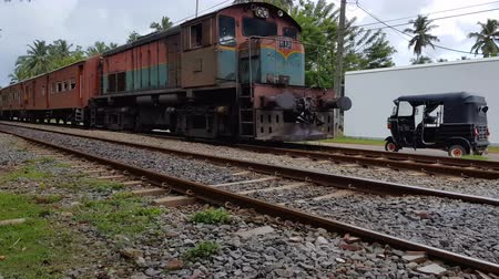 mozdony : Wadduwa, Sri Lanka - May 12, 2018: Passenger train passes through residential area in Sri Lanka.