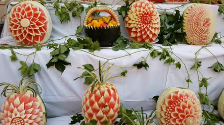 резной : Large fresh watermelons with carved decorations on the counter. Decorative watermelon carving. Fruit cutting art