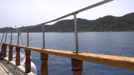 парусное судно : View through railing of cruise ship on sunny day at sea. Turkish coast near the island of Kekova. Slow motion Стоковые видеозаписи