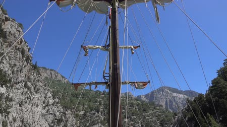 такелаж : View of the mast of yacht sailing among mountain cliffs on the background of a blue sky