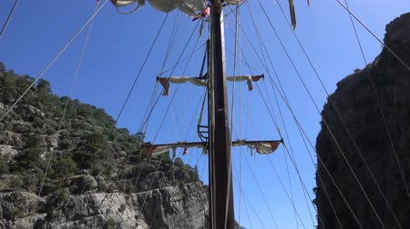 縛ら : View of the mast of yacht sailing among mountain cliffs on the background of a blue sky