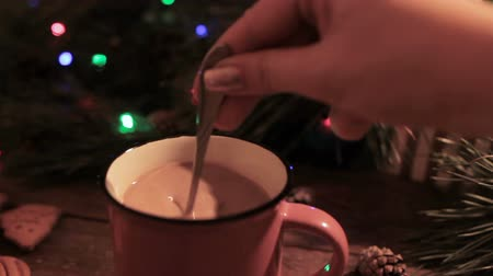 bolinho : Delicious Christmas holiday with latte. Close up process woman stirring up hot drink and put out the spoon after that. Festive blurred background of illuminated pine on backdrop