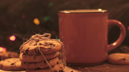 bolinho : Delicious Christmas holiday with latte and cookies. Close up cup of warm drink and sweet scones on festive illuminate fairy lights background. Happy celebration, cozy xmas evening concept Vídeos