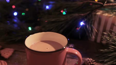 lentejoula : Delicious Christmas holiday with cup of latte. Just stired up hot drink stays on wooden table on festive background of illuminated pine, gift box and gingerbread scones nearby, close up Stock Footage