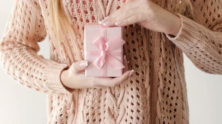 new clothes : girl holding and stroking a present in a gift box. surprise congratulation celebration reward gratitude concept. Stock Footage