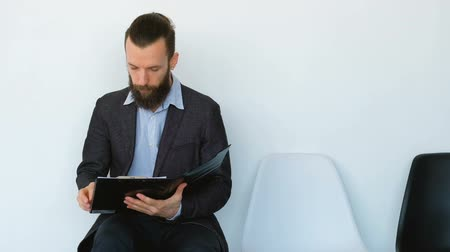 rozhovor : Business guy waiting for appointment. Young bearded man sitting looking through documents. Annual report in hands. Dostupné videozáznamy